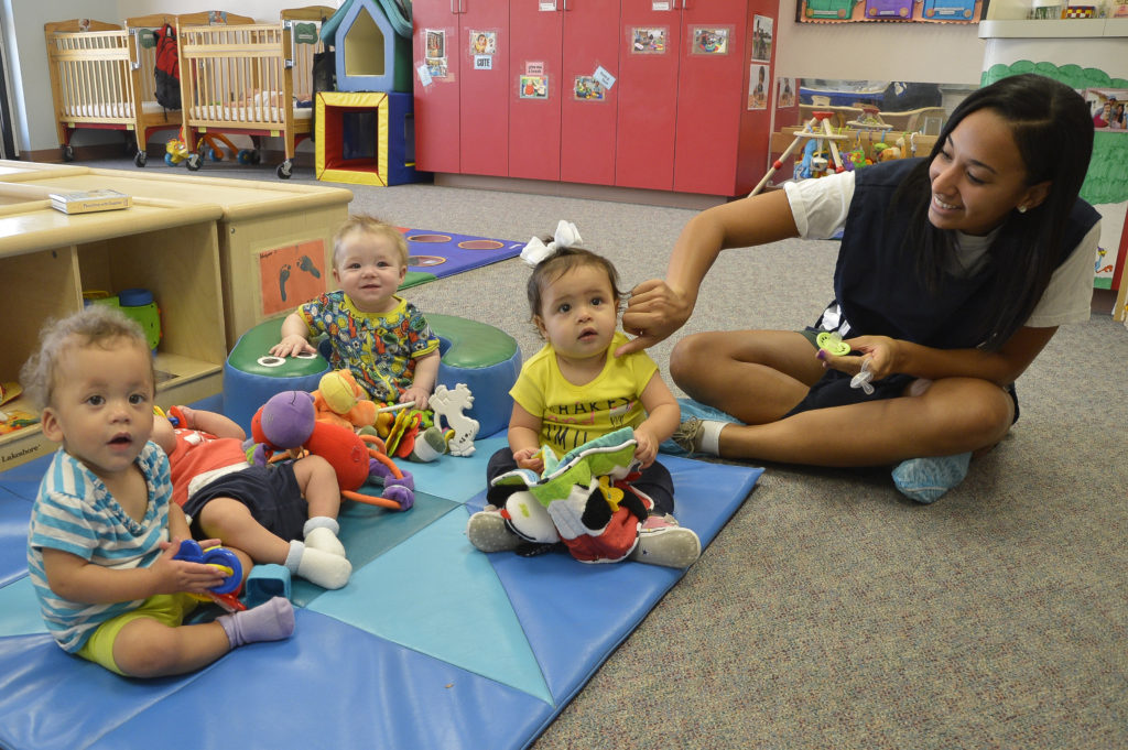 A teacher and three babies play on the floor