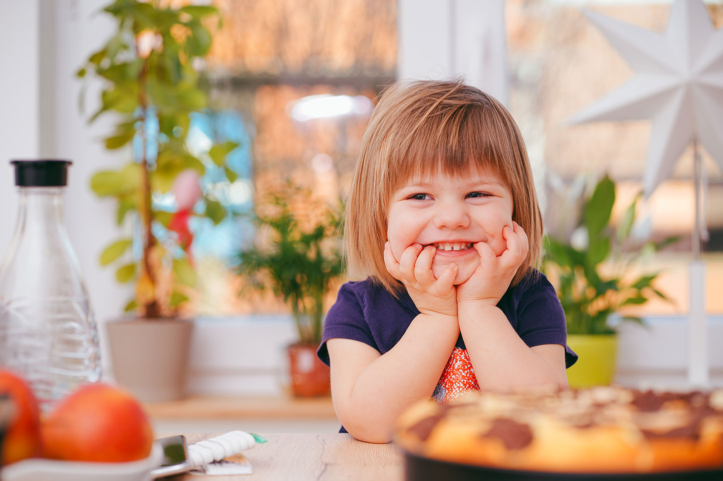 smiling toddler in kitchen with blurred pizza