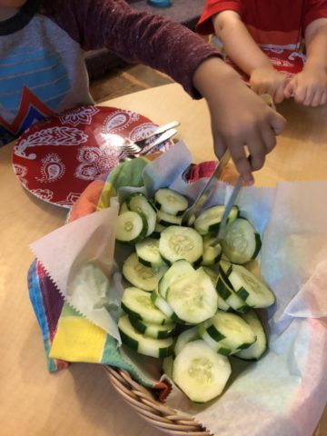 A child grabs a cucumber with tongs