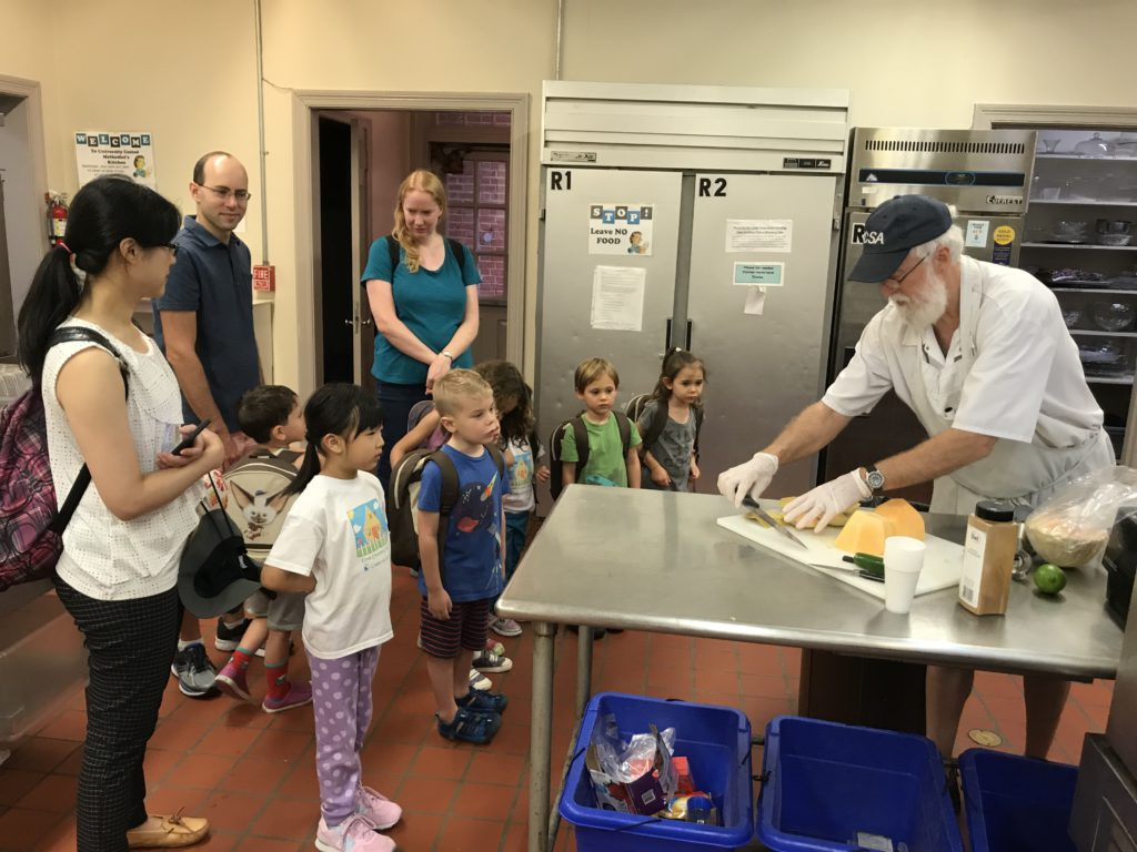 A man makes food as children and adults watch