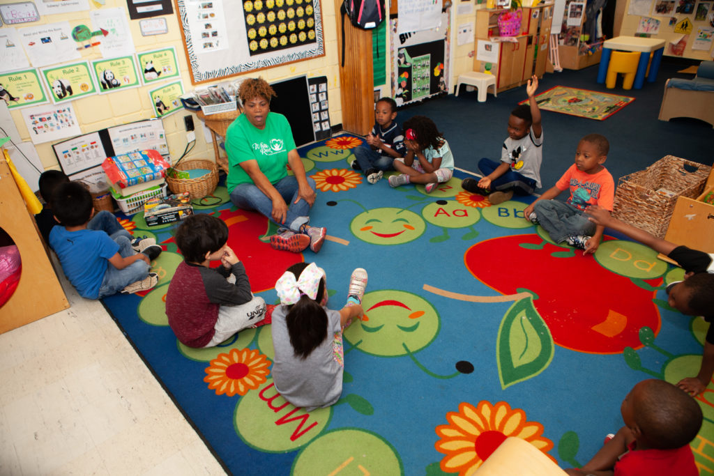 A teacher and several students sit in a circle on a rug