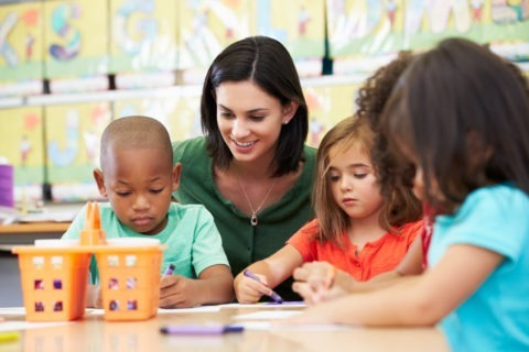 A teacher sits with a young boy and girl as they color