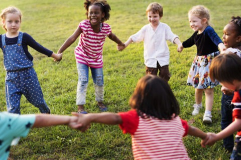 Eight kids stand in a circle outside holding hands