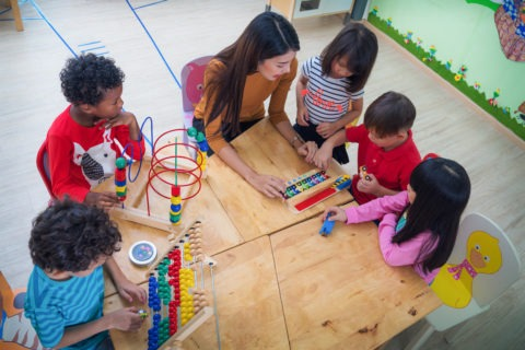 Teacher sitting at table with five young children exploring toys
