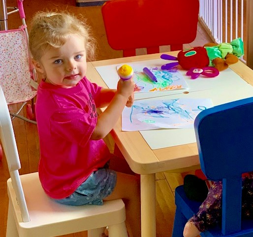 A young girl sitting at a table coloring