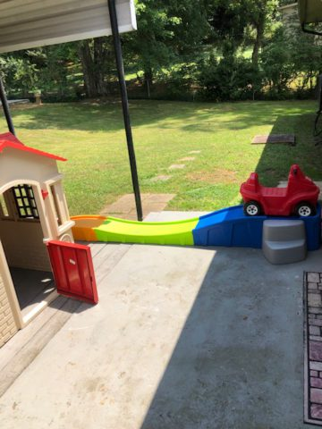 Outside Shining Stars features a playhouse and toy roller coaster with toy car for small children