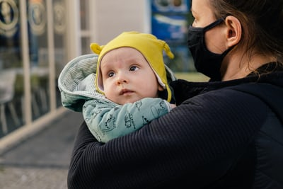 A woman wearing a mask holds a baby