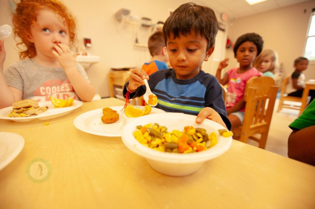 Young children eating and serving food in a classroom