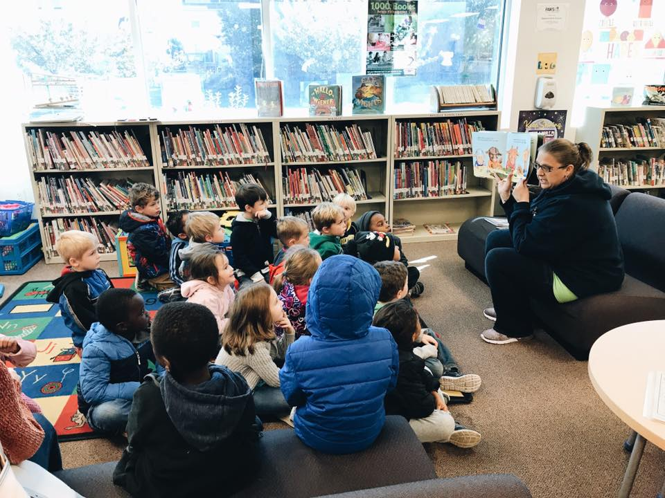 An adult woman reads to a group of children