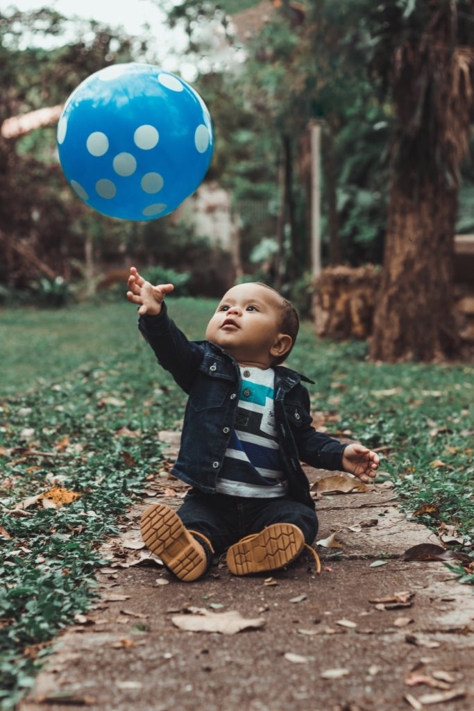 toddler reaching for blue ball in air