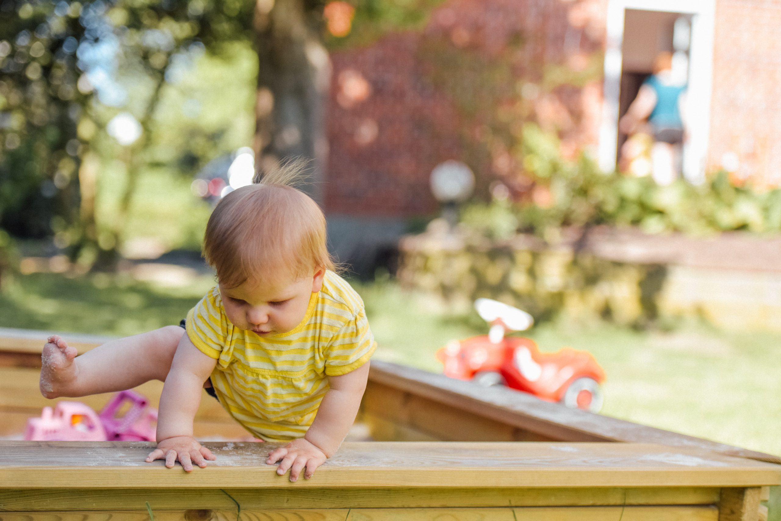 A baby climbing out of a play pen
