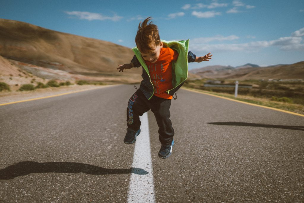 young boy jumping in empty road with mountains behind him
