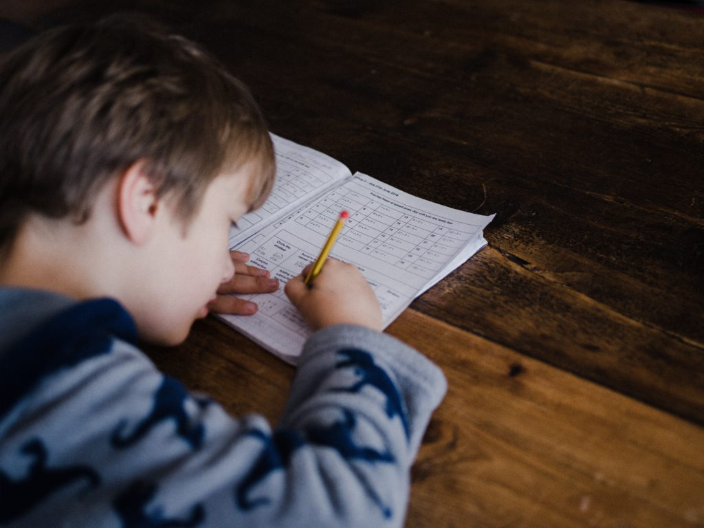 Young boy does a worksheet with a pencil