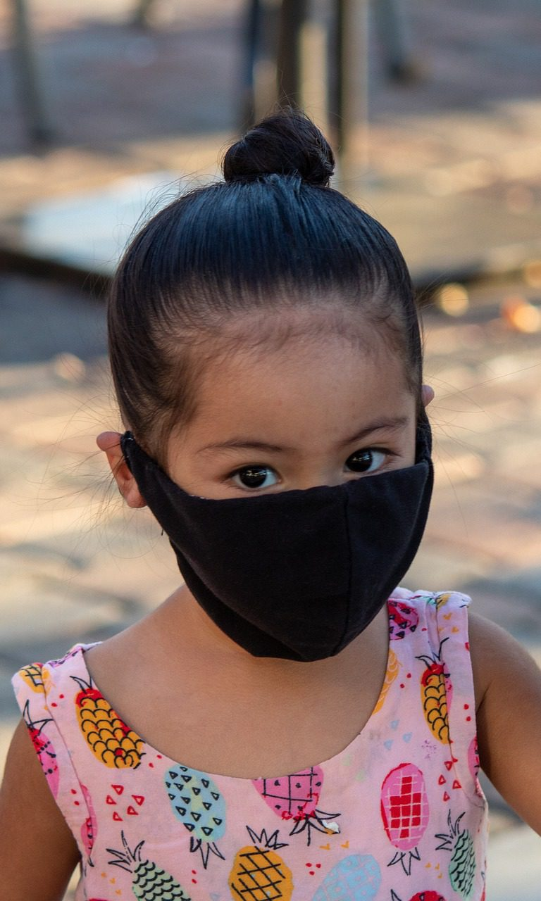 Young girl wearing mask holding hand of adult