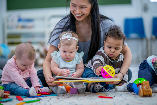 A woman reading to three babies