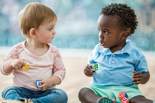 2 young toddlers playing with blocks looking at each other