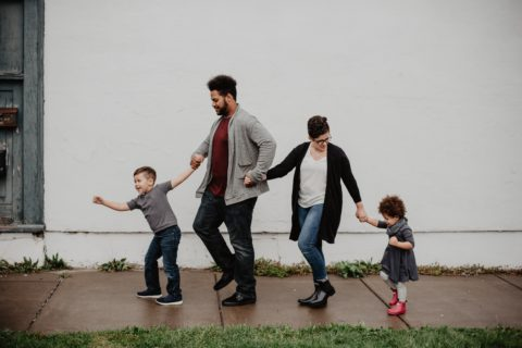 Two adults hold hands with two children