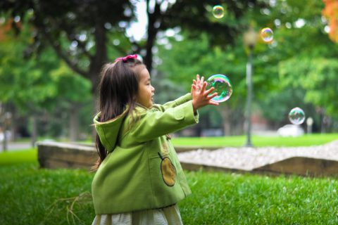 little girl reaching out to bubble in park