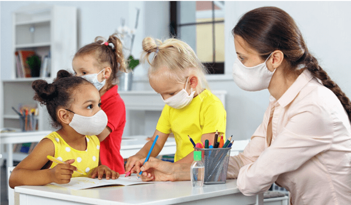 3 young children in masks in classroom coloring with teacher with mask on