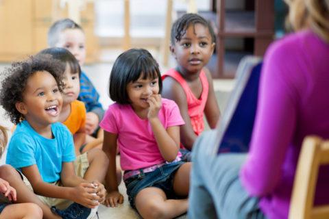 teacher reading to children on floor