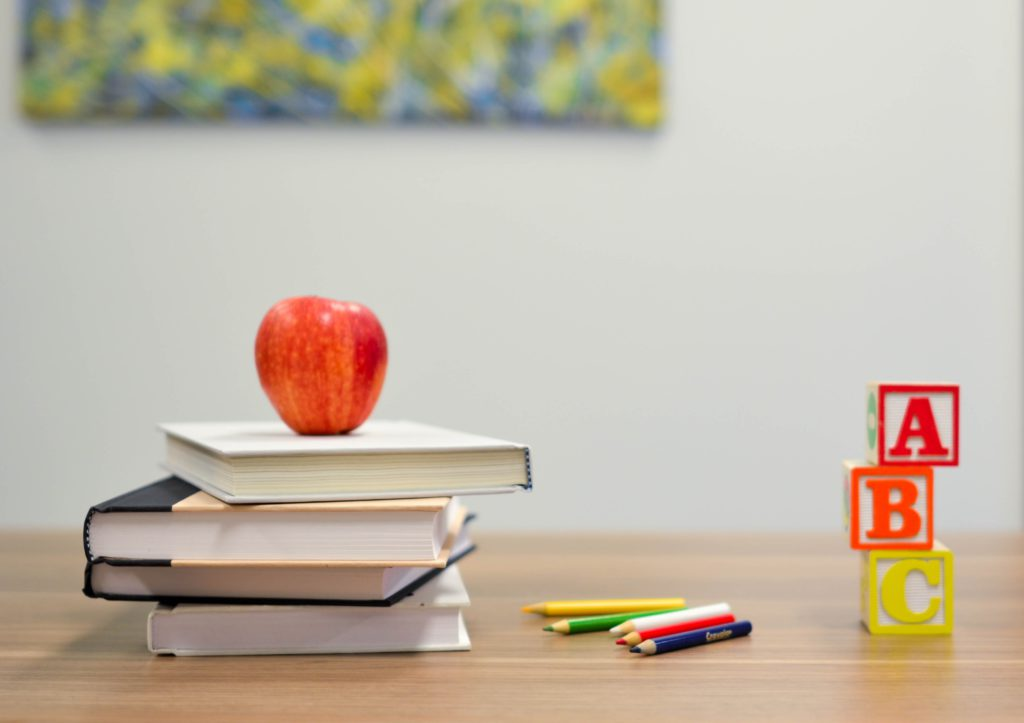 An apple sits on top of a pile of books, next to pencils and blocks
