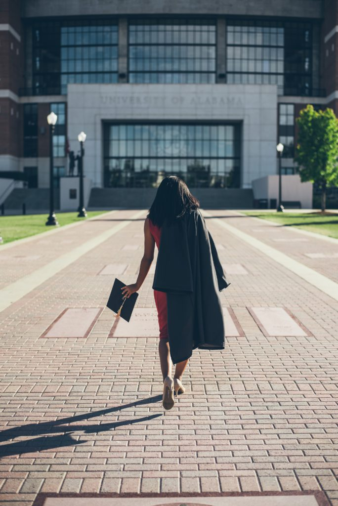 Woman walking towards a building wearing a cap and gown