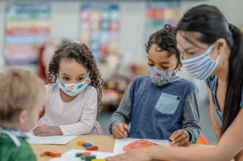 young kids and teacher wearing masks in classroom