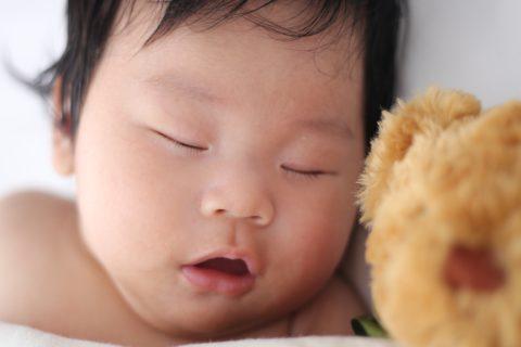 A baby sleeping next to a stuffed bear