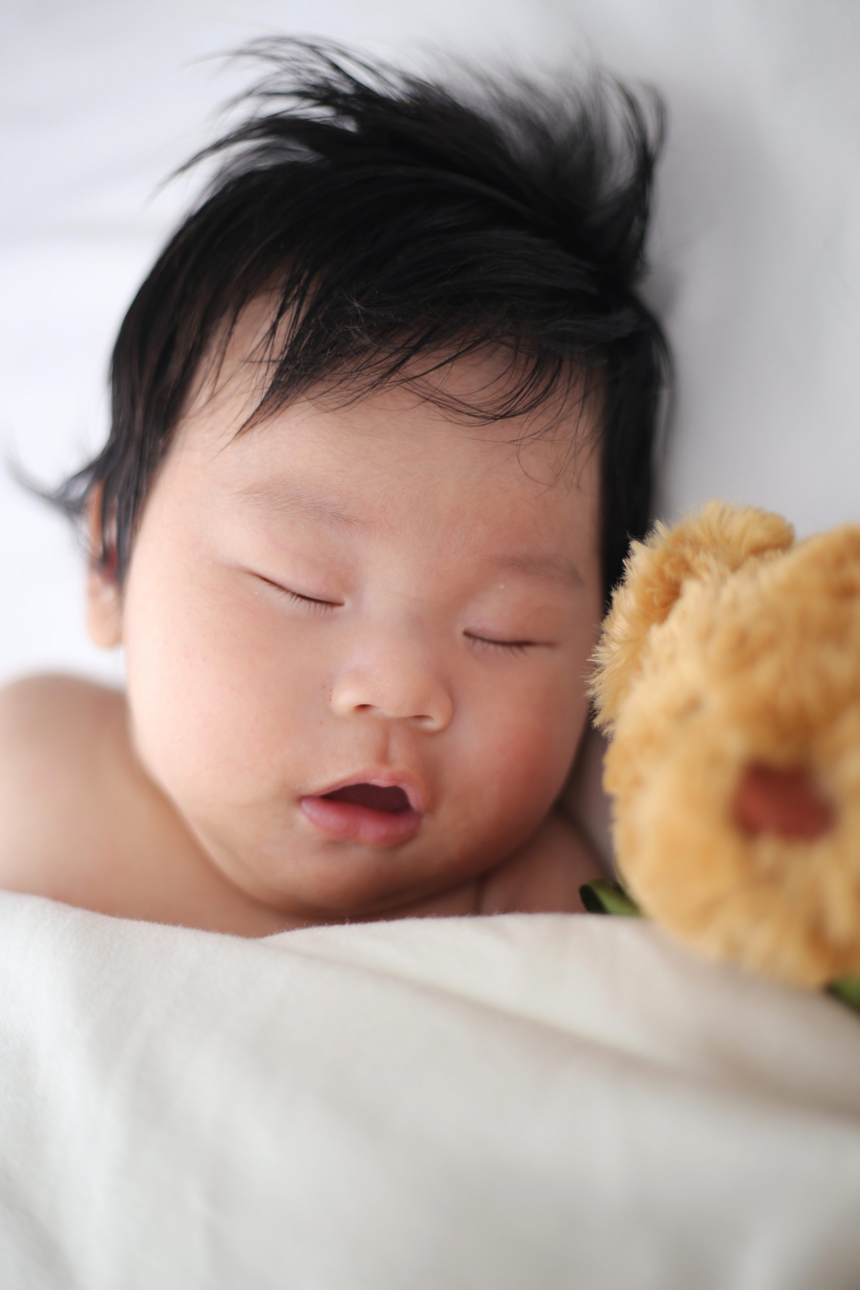A baby sleeping next to a stuffed bear