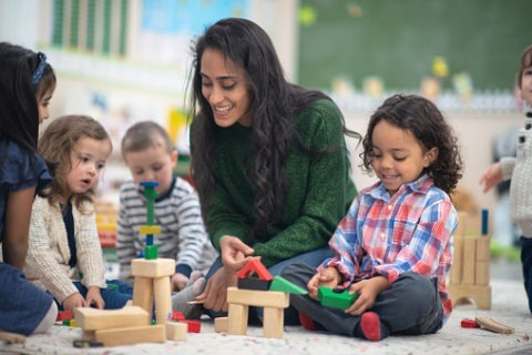 Teacher plays with blocks on floor with 4-5 young children