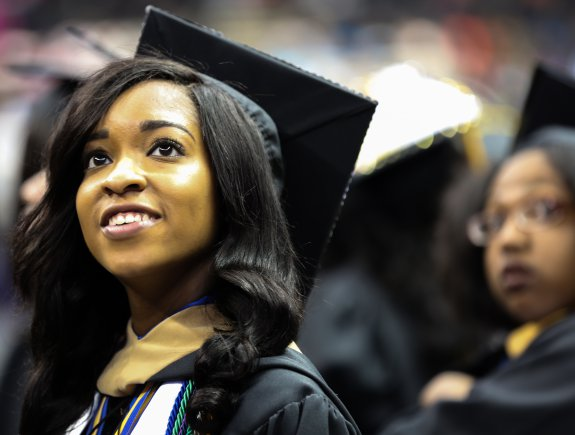 A woman in a cap and gown at a graduation ceremony