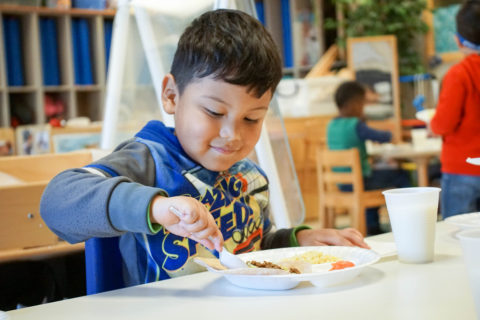 Boy eats food seated at a table