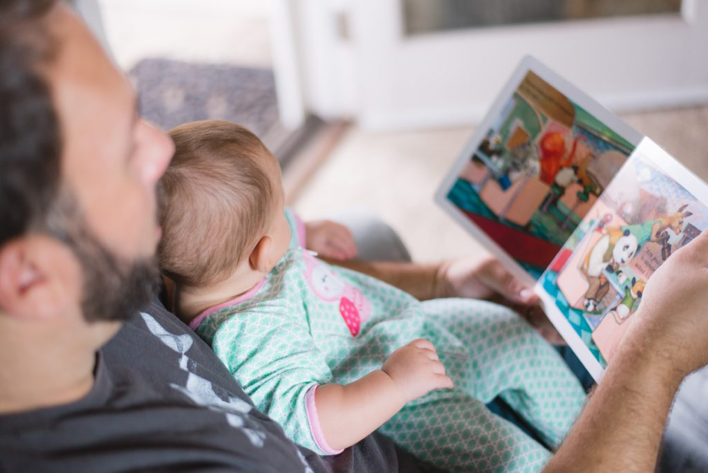 a man reads a picture book to a baby