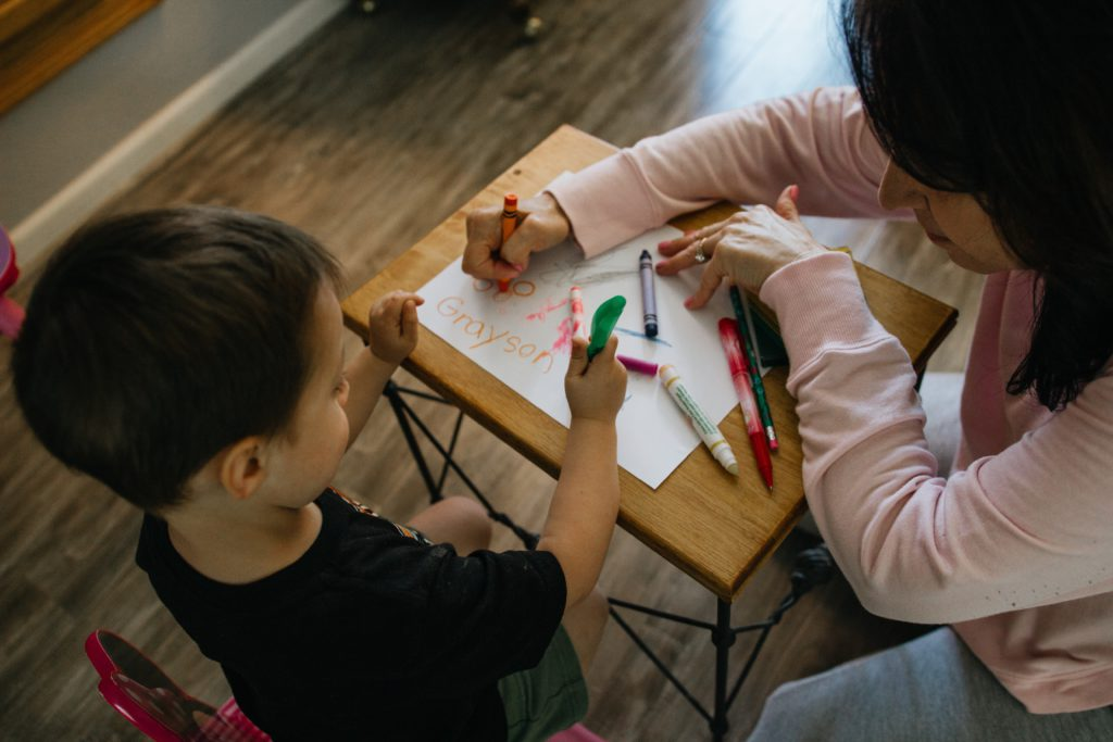 A woman and young boy drawing